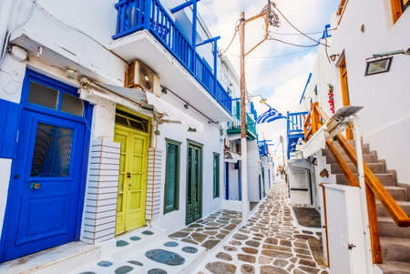 Old Traditional greek street of Mykonos with white houses colourful doors and balconies, Greece