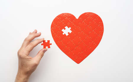 Top view of hand holding last piece near unfinished puzzle in form of heart on white background