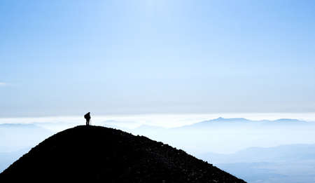 Silhouette of mountain with one hiker standing on top