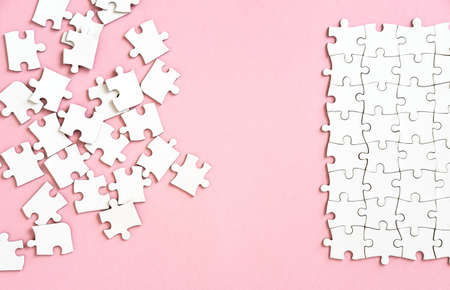 white puzzle pieces on pink background