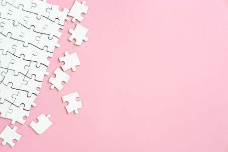 White jigsaw puzzle pieces in corner on pink background with copyspace