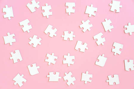 Background of of white jigsaw puzzle pieces on pink, top view