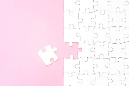 Last unconnected piece of white puzzle on pink background