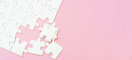 white puzzle pieces on pink background with copyspace