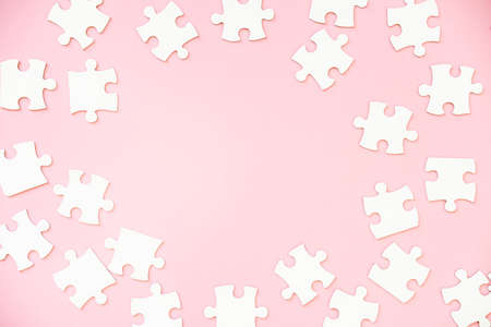 Background of white jigsaw puzzle pieces on pink, top view