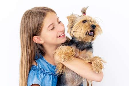 Friendly female child smiling to terrier dog Standard-Bild