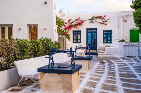 Traditional greek street with old wells of Mykonos with white houses, Greece