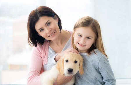 Sweet daughter and mother with lovely golden retriever dog Stockfoto