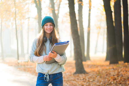 Cute student with books and backpack in autumn park
