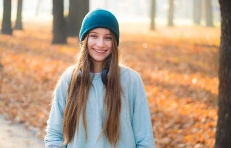 Smiling girl with headphones in nature