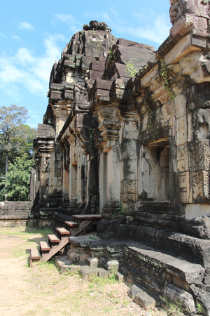 The ruins of a temple in the complex of Angkor, near the ancient city of Siem Reap. Black and gray stones, jungle around
