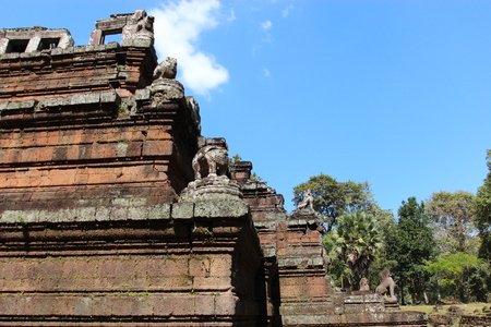 Brick and stone masonry of the ancient walls of the Cambodian temple, with reliefs and sculptures, pillars and columns on a natural background