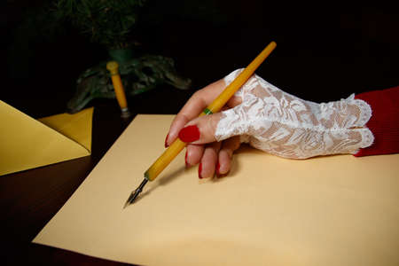case sheet: Lady at the age writes letter with quill on yellow paper Stock Photo