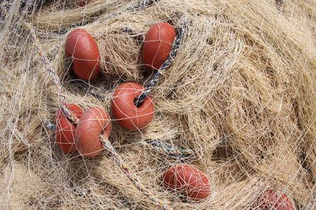 fishermans net: Fishing net with red bobber, fishermans equipment