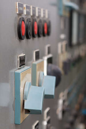 switches: Part of old power plant control panel with switches and red buttons