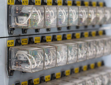 carrera de relevos: Row of  old  white Relay actuators with yellow marks