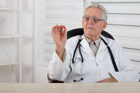 dispensary: Old doctor with glasses observe and study red  pill Stock Photo