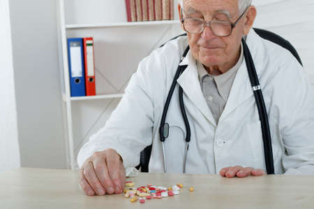 observe: Old doctor with glasses observe lot of  pills