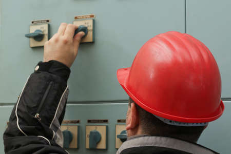 turn on: Engineer with red helmet turn on  the power switch in power plant control center