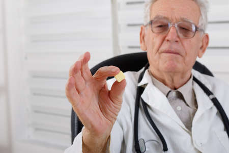 doctor giving glass: Old doctor with glasses observe yellow pill Stock Photo