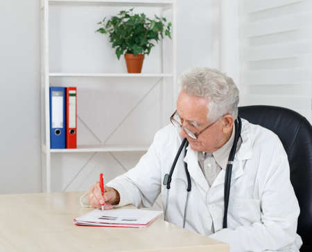 doctor giving glass: Old doctor with glasses writing  recipe in  consulting room