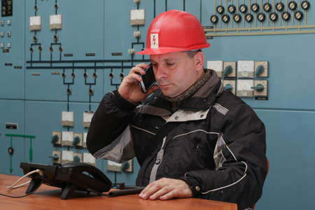 casco rojo: Engineer with red helmet make mobile phone call in the power plant control center