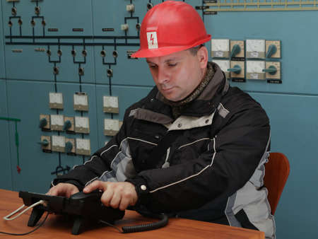 control center: Engineer with red helmet prepare to make phone call in the power plant control center Stock Photo