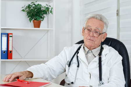 doctor giving glass: Old doctor with glasses thinking in consulting room