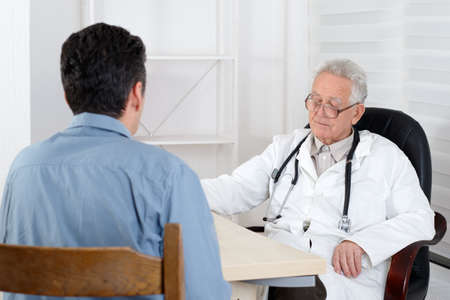 doctor giving glass: Male patient having consultation with old Doctor in office