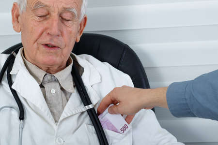 bribes: Old male doctor taking bribes from patient