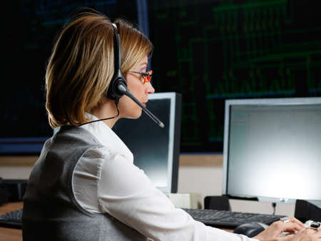 control center: Female operator  with headphone in power distribution control center
