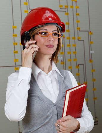 casco rojo: Mujer sonriente joven con el casco de la llamada marca roja en el centro de control de distribución de energía