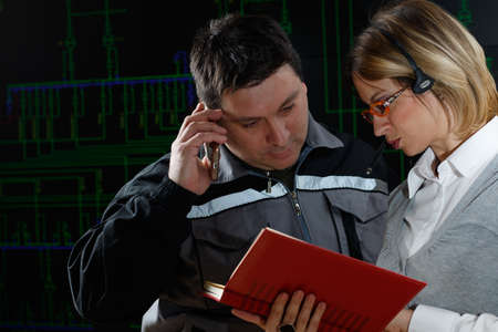 power distribution: Man and woman are making consultation in power distribution control center Stock Photo