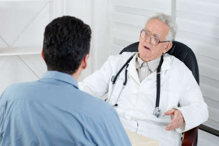 consulting: Male patient having consultation with old Doctor in consulting room