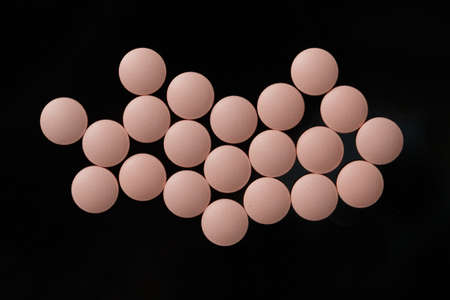 antibiotic pink pill: Group of pink pills  isolated on black