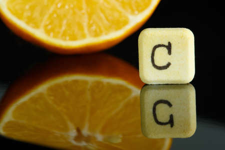 vitamins: Vitamin C and lemon with reflection in black Stock Photo