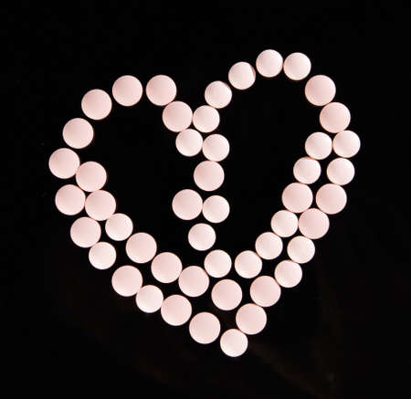 antibiotic pink pill: Heart shape pink  pills isolated on black