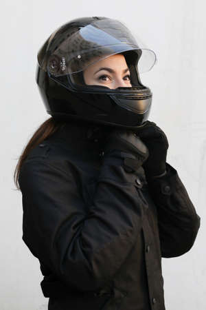 motorrad frau: Das M�dchen Motorradfahrer sitzt auf dem Motorrad und einen Helm binden