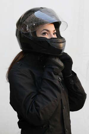 motociclista: El motociclista chica se sienta en la motocicleta y atar un casco