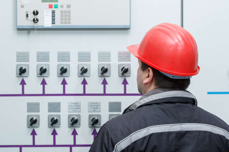 control center: Engineer in red helmet reading instruments in power plant control center Stock Photo