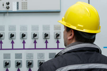 control center: Engineer in yellow helmet reading instruments in power plant control center