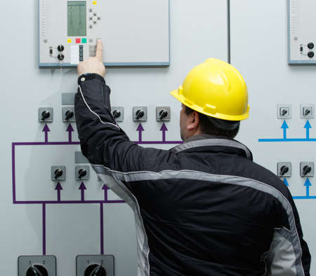 automatically: Engineer in yellow helmet give command in power plant control center