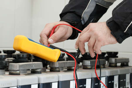 ammeter: Electrician check  battery voltage with yellow multimeter