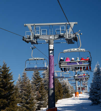 chair on the lift: Ski chair lift with skiers and snowboarders