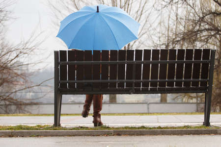 Rainy day  woman siting on bench and holding blue umbrella