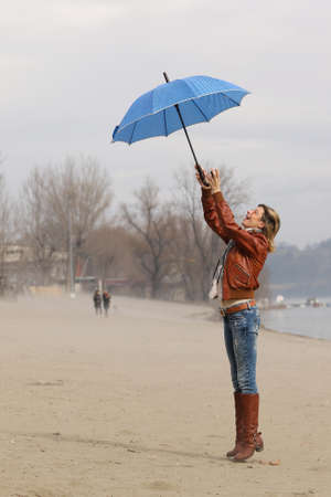 windy day: The young  woman with blue umbrella on windy day