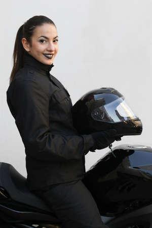 motociclista: El motociclista chica se sienta en la motocicleta