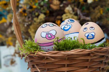 la cara de huevo bebé heppy Pascua en cesta de mimbre