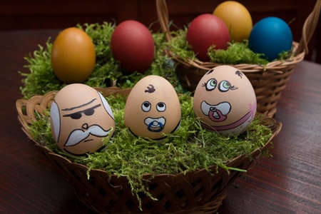 happening: Easter  egg face family in wicker basket, grandfather and two grandson