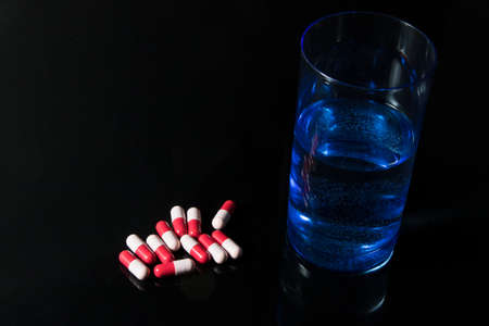 pharmacologist: Red and pink antibiotic capsule and glass of water  on black